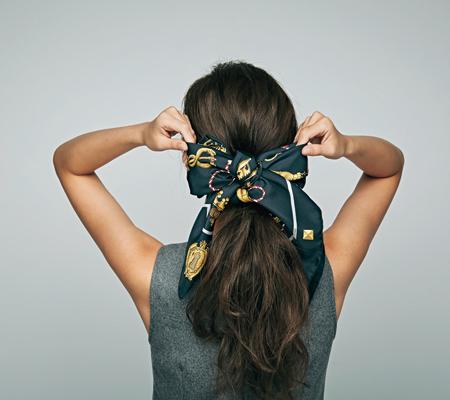 スカーフを斜めに折り畳んで細長くし、毛束にちょう結びする。