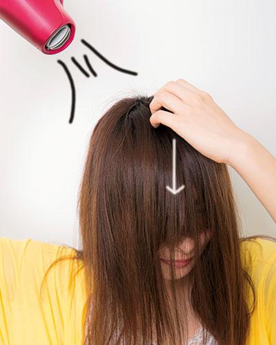 (5)根元のくせをリセットしてフラットにするため、つむじを中心に前髪を放射状に下ろして、上から風を当てる。指で地肌をこすりつつ、髪は下へ。